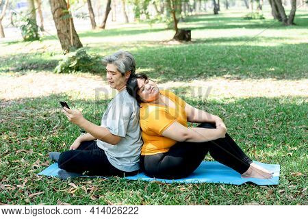 Asian Couple, Fat Woman And Man Are Sitting Relaxation In The Shardy Park, Husband Using A Mobile Ph