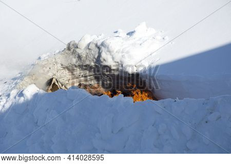 Disposal Of Trash Through Burning Trash In The Snow. A Place For Incineration Of Household Waste In