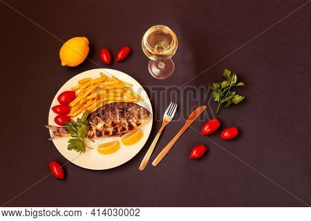 Delicious Roasted Dorado  Fish, Glass Of White Wine, Lemon, Parsley And Tomatoes On Dark Background.