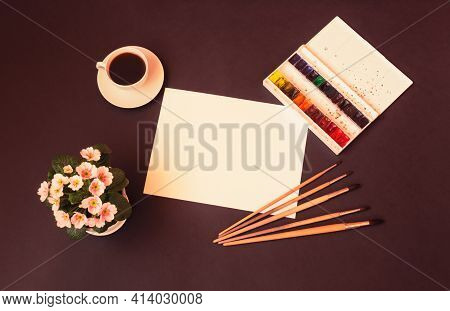 Watercolor Paints, Brushes For Painting, Paper Sheet, Cup Of Coffee And Primrose Flower On  Dark Bac