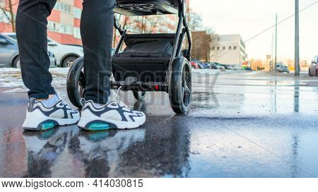 Mom Walks On The Street With A Baby In A Stroller, Stroller Close-up, Bottom View