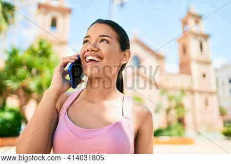 Young beautiful hispanic sporty woman wearing fitness outfit smiling happy and natural calling using smartphone at the town