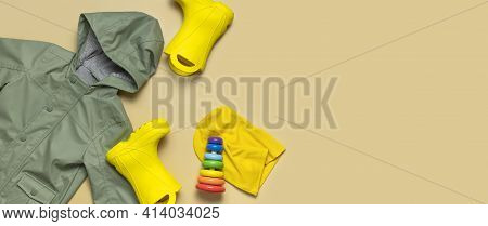 Baby Yellow Rubber Boots, Green Hooded Jacket, Wooden Toy Pyramid, Yellow Hat On Beige Background. W