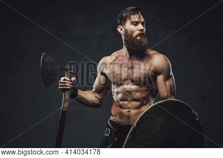 Northern Warrior With Axe And Shield In Dark Background