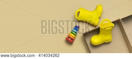 Baby Yellow Rubber Boots In Cardboard Craft Box, Multi-colored Wooden Toy Pyramid On Beige Backgroun