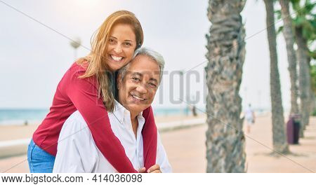 Middle age hispanic couple smiling happy and hugging walking at street.