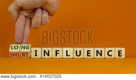 Short Or Long Influence Symbol. Businessman Turns Cubes And Changes Words 'short Influence' To 'long