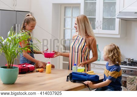 Smiling caucasian mother with son and daughter preparing packed lunches and school bags in kitchen. happy family spending time together at home.