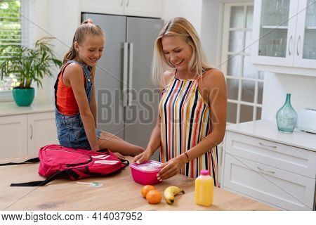 Smiling caucasian mother preparing daughter packed lunch in kitchen. happy family spending time together at home.