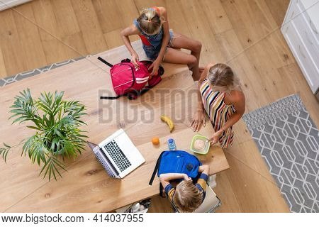 High angle view of caucasian mother with son and daughter preparing packed lunches in kitchen. happy family spending time together at home.
