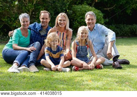 Portrait of caucasian parents, grandparents and grandchildren sitting in garden smiling to camera. happy three generation family spending time together at home.