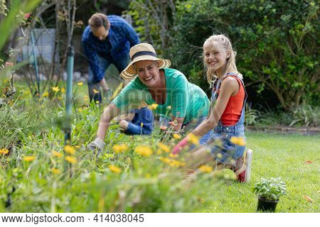 Smiling caucasian granddaughter and grandmother planting in garden, gardening with their family. happy three generation family spending time together at home.