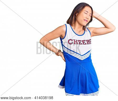Young beautiful chinese girl wearing cheerleader uniform suffering of neck ache injury, touching neck with hand, muscular pain