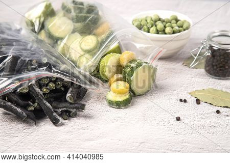 Close-up Of Bags Of Frozen Vegetables-string Beans And Zucchini And Frozen Green Peas On A Light Bac