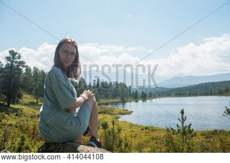 Woman resting at mountain lake in summer, Altai mountains
