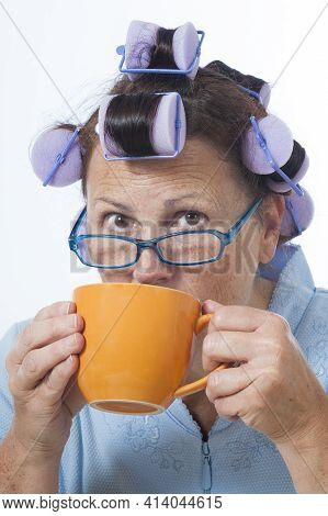 Vertical Shot Of A Mature Woman With Hair Curlers Drinking Coffee.  This Is A Revised Image.