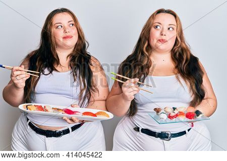 Plus size caucasian sisters woman eating sushi using chopsticks smiling looking to the side and staring away thinking.