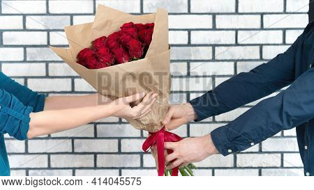 A Man In A Suit Gives The Girl A Gorgeous Bouquet Of Red Roses As A Gift For Valentine's Day, Annive