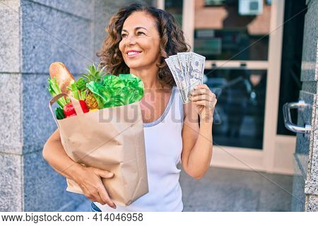 Middle age hispanic woman smiling happy holding a grocery shopping bag full of groceries and american dollars at the city.