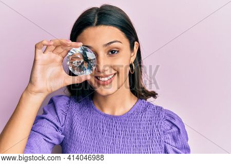 Young hispanic woman holding brilliant diamond stone looking positive and happy standing and smiling with a confident smile showing teeth