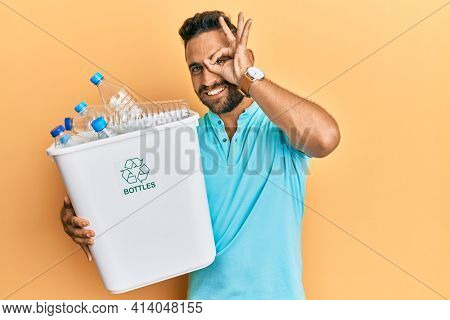 Handsome man with beard holding recycling wastebasket with plastic bottles smiling happy doing ok sign with hand on eye looking through fingers