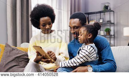 Portrait Of Cute African American Family Parents And Little Girl Kid Sitting On Couch In Living Room