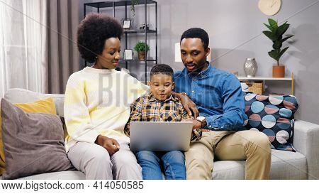 Happy Young Nice African American Family Spending Time Together Gathered At Home On Sofa Using Compu