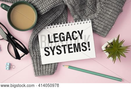 Legacy Systems Is Written In A White Notepad Near A Calculator, Coffee, Glasses And A Pen. Business