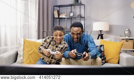 Portrait Of African American Joyful Young Male Parent Having Fun With Small Son Sitting On Sofa In A