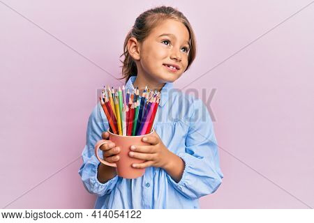 Little beautiful girl holding colored pencils smiling looking to the side and staring away thinking.