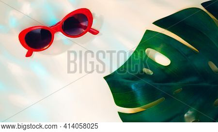 Red Sunglasses And Monstera Leaf On Sand Colored Background In Sunrays
