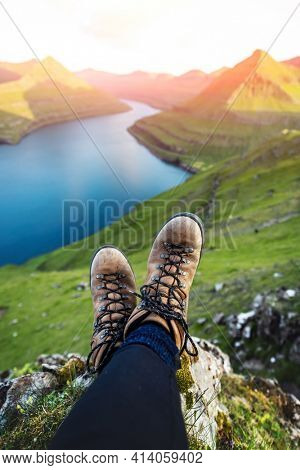 Boots of lonely tourist over majestic fjords of Funningur