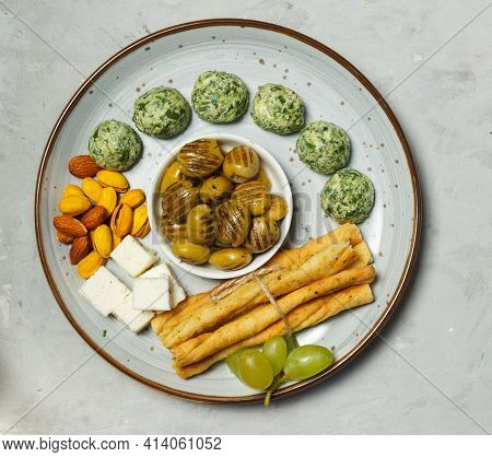 A Plate Of Tapas In Close-up, Overhead, Grey Background.dried Olives, Pistachios With Saffron , Brea