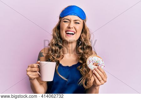 Young blonde girl wearing sleep mask and pyjama having breakfast smiling and laughing hard out loud because funny crazy joke.