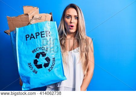 Young beautiful blonde woman recycling holding paper recycle bag full of paperboard scared and amazed with open mouth for surprise, disbelief face