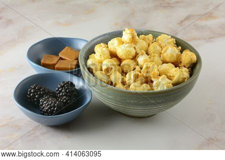 Caramel Popcorn With A Hint Of Blackberry Liqueur In Snack Bowl And Caramel Squares And Fresh Blackb