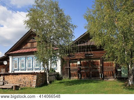 Russian Village In Summer. View Of The Old Traditional Wooden House With Carved Windows, Barn And Bi