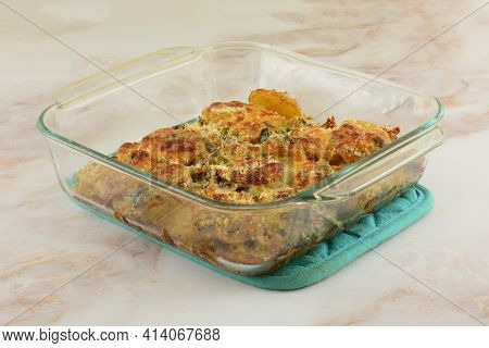 Baked Poblano Pepper And Potatoes Au Gratin Casserole In Glass Baking Pan On Pot Holder On Table