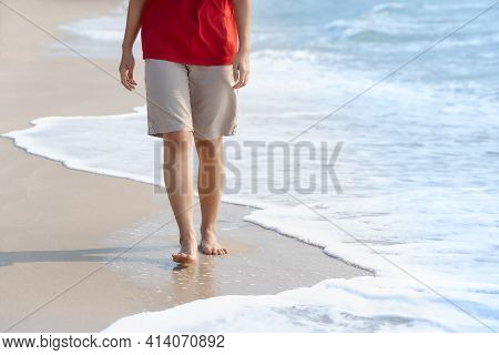 Young Woman's Bare Feet With A Wave Coming And Enjoying To Travel On Tropical Beach In Sunlight. Hea