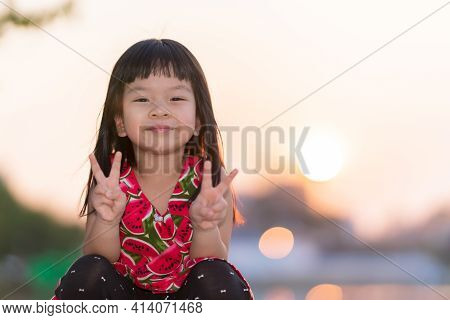 Girl Sitting With Sweet Smile. Child Raised Two Fingers And Look At Camera. Natural Blurred Backgrou