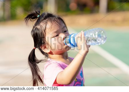 Asian Little Girls Drink Some Water From Plastic Bottles. Child Sweat From Exercise In Hot Weather.