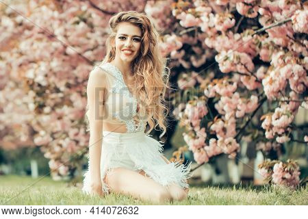 Beautiful Young Happy Woman In White Glamour Dress In Spring Blossom Park. Beauty Girl On Blooming S