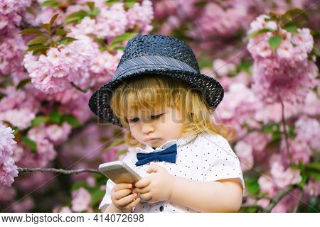 Small Baby Boy In White Shirt And Retro Hat With Bow Tie With Blonde Hair Playing On Mobile Phone In