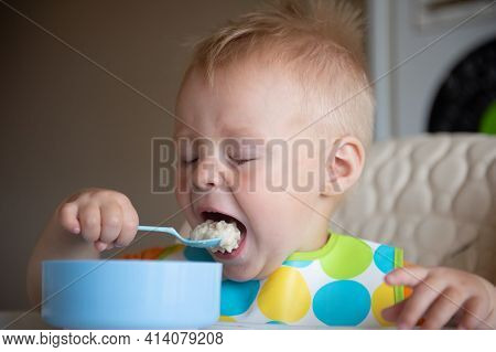 Focused Adorable Toddle In Colorful Bib Sitting In Highchair And Eating Porridge With Spoon.