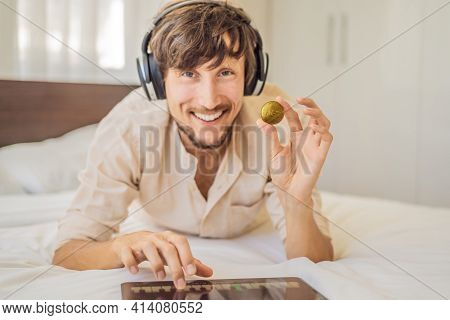 Young Man, A Digital Artist, Dj Creates Digital Art On A Tablet At Home And Shows A Coin With The In