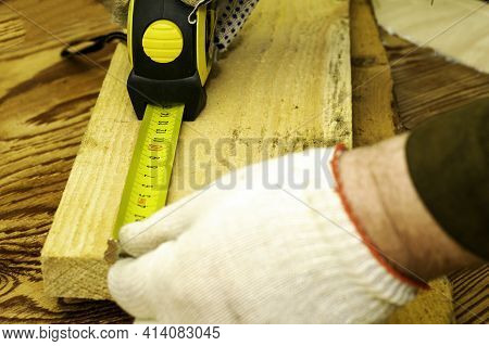 A Person With A Measuring Tape Measures A Board