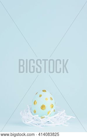 Simplicity And Minimal Design Of Easter Egg With Gold In White Nest On Blue Background, Vertical.