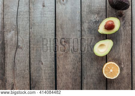 Healthy Eating Concept Flat Lay. Mediterranean Diet, Wooden Background With Avocado Halves, Whole Av