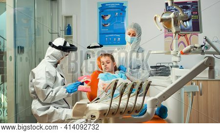 Stomatologist In Ppe Suit Holding Plaster Model Of The Mandible Speaking With Girl