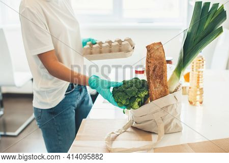 Side View Photo Of A Caucasian Woman Unpacking Products Wearing Medical Gloves At Home